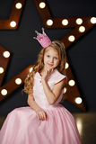 Portrait of a blonde girl in a pink dress and crown on the backg Stock Photography