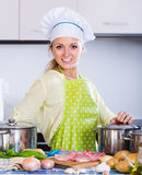 Portrait of  blonde girl preparing meat indoors Royalty Free Stock Image
