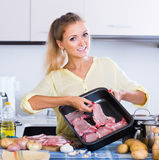 Portrait of  blonde girl preparing meat indoors Stock Images