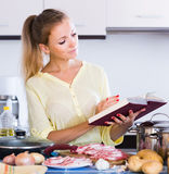 Portrait of  blonde girl preparing meat indoors Stock Photography