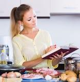 Portrait of  blonde girl preparing meat indoors Stock Photography