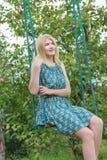 Portrait of blonde girl in silk sundress sitting on handmade swing Stock Photos