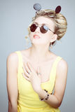 Portrait of a blonde girl with sunglasses. Studio photo of blonde in yellow dress and sun glasses Royalty Free Stock Images