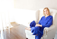 Portrait of a blonde girl wearing blue dress relaxing on the chair Stock Images