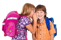 Portrait of a blonde girl whispering in boy's ear Stock Photos