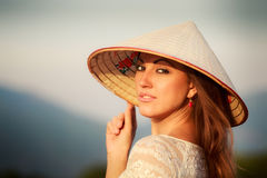 portrait of blonde girl in white Vietnamese hat against blur sky Stock Images