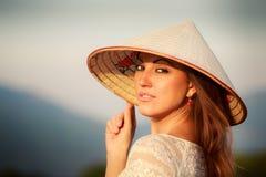 portrait of blonde girl in white Vietnamese hat against blur sky Stock Images