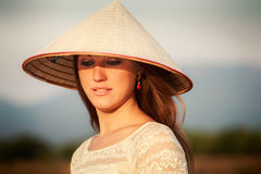 portrait of blonde girl in white Vietnamese hat against blur sky Stock Photos