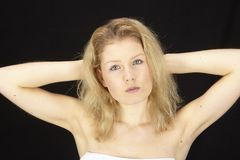 Portrait of blonde-haired woman. A portrait of a blonde-haired woman in froont of a black background Royalty Free Stock Photos