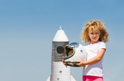 Portrait of blonde little girl in an astronaut costume with toy rocket dreaming of becoming a spacemen Royalty Free Stock Images