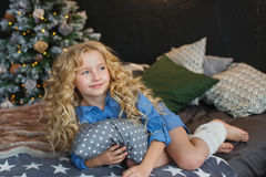 Portrait of blonde little girl in blue dress lies and looks side on a bed in Christmas dark room Stock Photo
