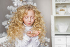 Portrait of blonde little girl looks and blows at a confetti at hands in Christmas studio Stock Photo