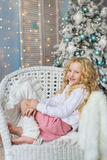 Portrait of blonde little girl sits and smiles on a chair in Christmas time. Portrait of blonde little girl sits and smiles on chair in Christmas time stock photo