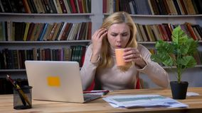 Portrait of blonde middle-aged caucasian woman choking and coughing in front of laptop in office on bookshelves. Background stock video footage