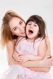 Portrait of blonde mom and sweet little daughter in pink dresses Stock Photo