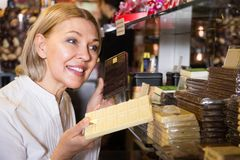 Blonde pensioner buying chocolate Royalty Free Stock Image