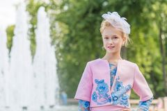 Portrait of a blonde in pink attire in a park outdoors. Vintage Royalty Free Stock Image
