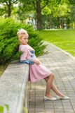 Portrait of a blonde in pink attire in a park outdoors. Vintage style Stock Image