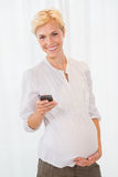 Portrait blonde pregnant using her mobile Royalty Free Stock Images