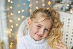 Portrait of blonde pretty little girl smiles in white sweater in Christmas Royalty Free Stock Images