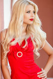 Portrait of a blonde in a red dress. Stock Image