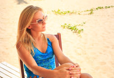 Portrait of blonde sad girl in sunglasses sits on chair on sand Royalty Free Stock Photos