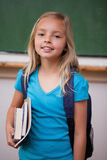 Portrait of a blonde schoolgirl holding her books Royalty Free Stock Photos