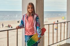 Portrait of a blonde schoolgirl skater posing with a skateboard while leaning on a guardrail against sea coast. Portrait of a blonde schoolgirl skater posing royalty free stock photography
