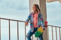 Portrait of a blonde schoolgirl skater posing with a skateboard while leaning on a guardrail against sky. Portrait of a blonde schoolgirl skater posing with a royalty free stock photo