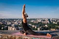 Portrait of blonde strong woman in sportwear doing workout stretching on the roof of skyscraper above the big city at early. Morning. Female sporty and sexy stock photos