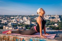 Portrait of blonde strong woman in sportwear doing workout stretching on the roof of skyscraper above the big city at early. Morning. Female sporty and sexy royalty free stock image