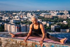 Portrait of blonde strong woman in sportwear doing workout stretching on the roof of skyscraper above the big city at early. Morning. Female sporty and sexy royalty free stock photography