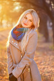 Portrait of blonde woman in autumn park with sunshine royalty free stock image