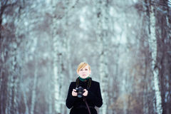 Portrait of a blonde woman in a black coat, with a camera in hand, on background blurred birch forest. Royalty Free Stock Photography