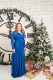 Portrait of a blonde woman in a blue dress with a gift near the clock and a Christmas tree Royalty Free Stock Photo