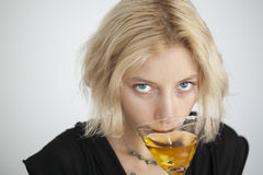 Blonde Young Woman with Beautiful Blue Eyes Drinks a Martini Stock Photography