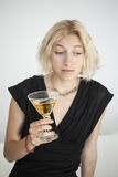 Blonde Young Woman with Beautiful Blue Eyes Drinks a Martini Stock Photo
