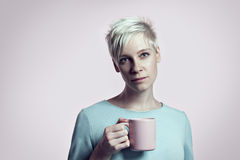 Portrait of blonde woman with cup of water, short hair background bright background. Pink and blue Royalty Free Stock Photos