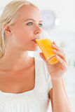 Portrait of a blonde woman drinking juice. Looking away from the camera Royalty Free Stock Image