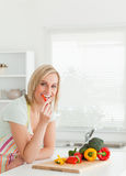 Portrait of a blonde woman eating red peppers Royalty Free Stock Photos