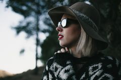 Portrait of blonde woman exploring nature in the middle of the forest. Close up. Young blonde woman with sunglasses, hat, and red lips enjoying discovering the Stock Image