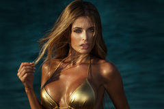 Portrait of blonde woman in gold bikini. Portrait of beautiful blonde woman with glamour makeup and long  hair. Sexy look. Girl in gold swimsuit Royalty Free Stock Images