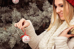 Portrait of blonde woman, hanging Christmas ornaments on spruce. Tree outdoors in yard near home Royalty Free Stock Image