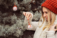 Portrait of blonde woman, hanging Christmas ornaments on spruce. Tree outdoors in yard near home Stock Photo