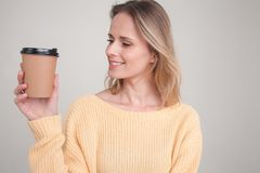 Portrait of blonde woman holding coffee cap in her hands, looking at it and smiling. wearing yellow sweater. poses against grey royalty free stock photography