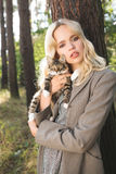 Portrait of a blonde woman with little kitten dressed in a gray coat Royalty Free Stock Photo
