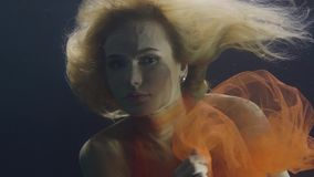 Portrait blonde woman in orange dress swimming underwater on dark background. Woman swimming like fairy mermaid under water and looking into camera stock video