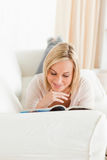 Portrait of a blonde woman reading a magazine Stock Images