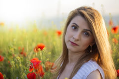 Portrait of blonde woman standing on field of poppies Stock Photo