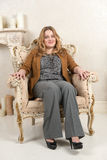 Portrait of a blonde woman in a suede jacket on a chair near the fireplace Stock Images